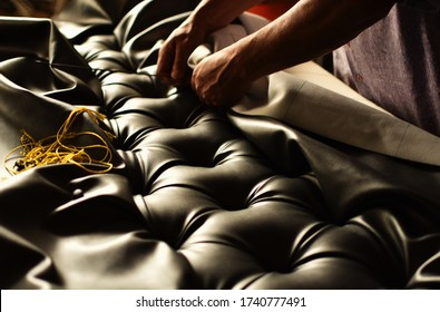 creative hands working on the upholstery of a capitoned headboard