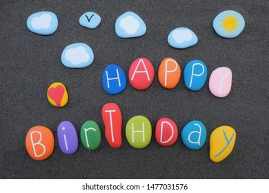 Creative Happy Birthay text with colored and carved sea stones over black volcanic sand
