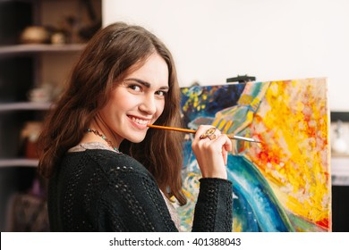 Creative happy painter paints a colorful picture. Closeup of painting process in art workplace. Smiling positive woman painter paints in her studio.
