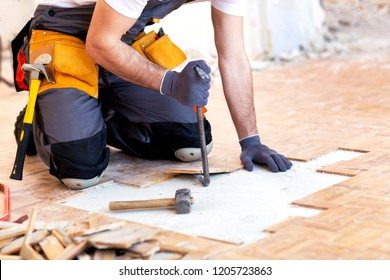 Creative and hard-working handyman tearing down the parquet structure