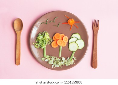 creative and healthy kids meal, cute trees made of fresh tasty vegetables and herbs, carrots, zucchini, onion, red pepper and rosemary, wooden spoon and fork on bright pink background, flat lay