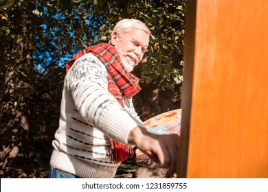 Creative hobby. Cheerful happy man smiling while enjoying painting a picture