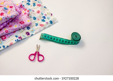 Creative hobby sewing colurful textile scissors and measuringtape sewing centimeter, Top view sewing accessory or tailor equipment, flatlay pink material flower print girly children white background