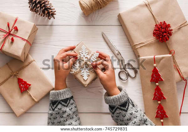 Creative hobby. Woman's hands wrap christmas holiday handmade present in craft paper with twine ribbon. Making bow at xmas gift box, decorated with snowflake. Scissors on white wooden table, top view.