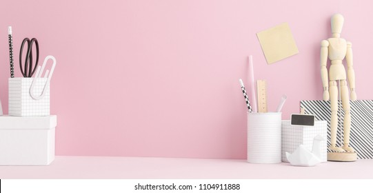 Creative home office desk with school supplies and pink wall.