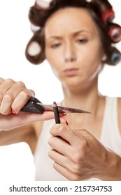 creative housewife with curlers sharpen her eye pencil with a big knife