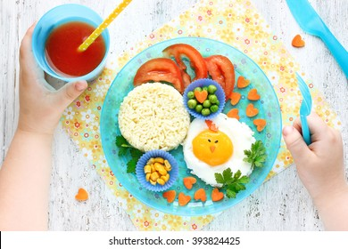 Creative idea for baby morning breakfast. Funny chick egg colorful vegetables fresh tomato juice rice garnish. Concept of healthy food for children top view
