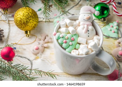 Creative idea for christmas drink, delicious hot chocolate with funny marshmallow snowman, christmas tree, rain dear, santa, on home background with xmas decoration copy space top view