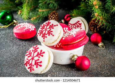 Creative idea for Christmas sweet treats, funny red and white macaron cookies decorated xmas ornament and snowflakes, dark rusty background with christmas tree branches and decorations, copy space