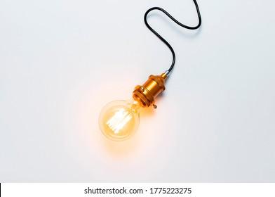 Kreatives Konzept, Designerlampe, modernes Interieur. Vintage-modische Edison-Lampe auf hellgrauem Hintergrund. Die oberste Ansicht flach legt Kopienraum. Licht, Elektrizität, Hintergrund mit Lampe