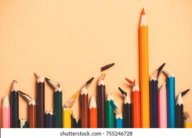 creative idea, concept of leadership and the truth of life, competition in business, leader among people with broken core, losers; pencils, colored pencil background
