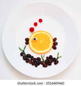 Creative idea for healthy food art.  Little, orange fish and seaweed on the white background.
