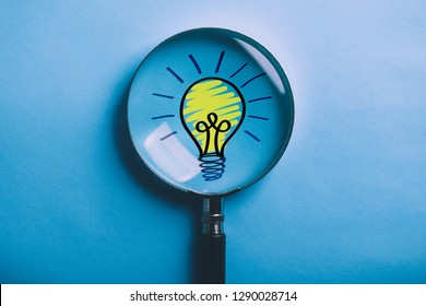 Creative Idea And Innovation Concept with magnifying on blue background.