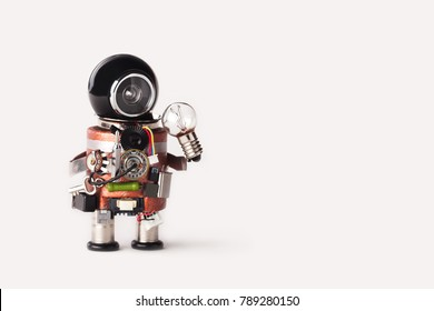 Creative idea inspiration concept. robot handyman with lamp bulb. Creative design cyborg toy, funny black helmet head. Copy space, white background.