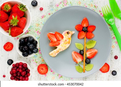 Creative idea for the kid's breakfast or dessert - flower of fresh strawberries kiwi and blueberries and toast with butter and sugar shaped bird hummingbird. Cute summer food, edible picture on plate