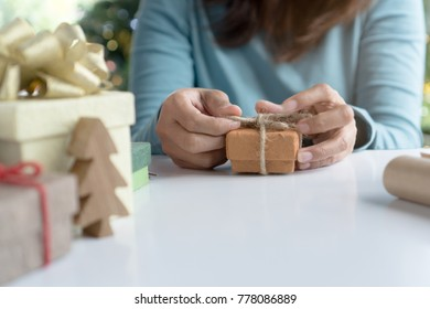 creative ideas handmade gift for holidays. boxes woman tying red bow decorated the craft presents box prepare for christmas night party.