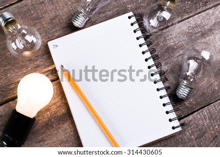 Creative ideas, notebook and pencil on wooden table