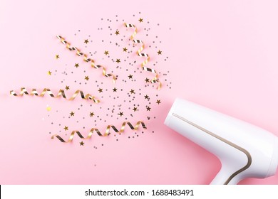 Creative image of a hair dryer blow up colorful confetti. Flat lay, top view.