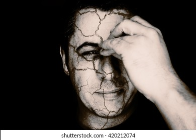 Creative image of a head portrait of a middle aged young looking male in black and white monochrome. The man holds his nose and sinus area with his fingers as cracks appear all over his skull and head