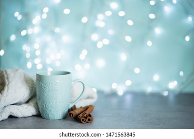 Creative image of hot chocolate with cream and cinnamon stick in a blue rustic ceramic cup. The concept of winter cozy holidays. Snow effect
