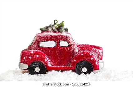 Creative image of a red Christmas miniature car with a Christmas tree on a white background; Christmas holiday; New Year