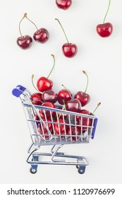 Creative image of ripe cherries in a shopping cart with copy space isolated on white background in minimal style. Concept of supermarket or fruit market shopping. Template for your text or design.
