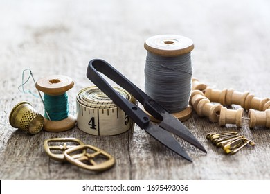 Creative image of seamstress ribbon tools, thimble and scissors for sewing on an old wooden surface. Concept. Selective focus.