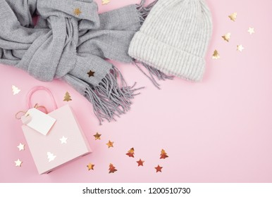 Creative image of warm woman accessories for cold winter weather and christmas gift box in pastel colors