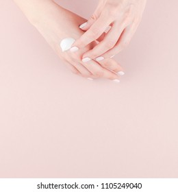 Creative image of woman moisturizing her hand with cosmetic cream lotion with copy space on millennial pink background in minimalism style. Square Concept for feminine blog social media beauty concept
