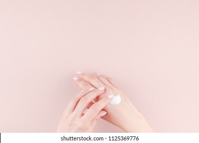 Creative image of woman moisturizing her hand with cosmetic cream lotion with copy space on millennial pink background in minimalism style. Concept template feminine blog, social media, beauty concept