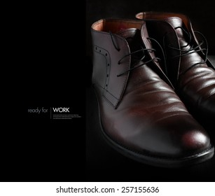 Creative image for work. Beautifully lit with natural light a pair of polished man's shoes against a dark background. Use for work, leaving home, travel, university,  job concepts. Boots. Copy space.