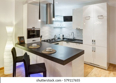 Creative interior of kitchen with furniture with neon violet light, room in beige, black and white colors. Two white cups on kitchen bar and chairs near. Elements of stones on wall.