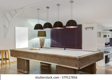 Creative interior of room with lounge zone with billiard table and lamps over it. Interior in white, purple and violet colors with art picture of wall. Place for playing in sport billiard.