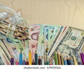 Creative Investment idea, Colorful pencils from glass jar on various money currency and pencils with pens arrange as line  on banknote, wood empty space table