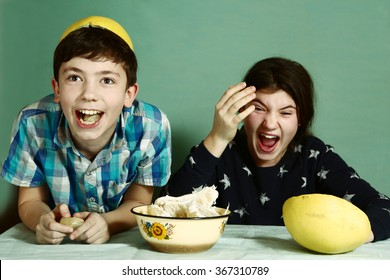 creative kids teenage siblings brother and sister  laughing peeling grapefruit make funny hat from it