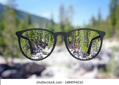 Creative landscape view though eyeglasses. Blurry background. Vision concept