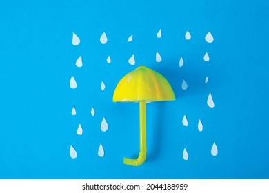 Creative lay flat umbrella in the rain made out of lemon, straw and paper, yellow on blue, summer rain - Shutterstock ID 2044188959