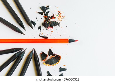 Creative layout of black and one red pencil on white background. Break through and be different concepts. Top view.