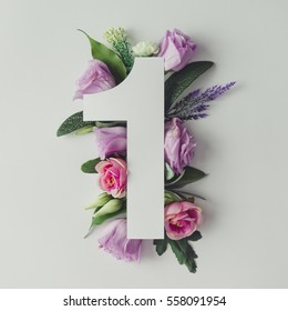 Creative layout with colorful flowers, leaves and number one. Anniversary concept.Flat lay.