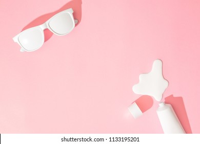 Creative layout with copy space, sunglasses and sunscreen or suntan lotion on pastel pink background. Minimal summer vacation concept. Flat lay.