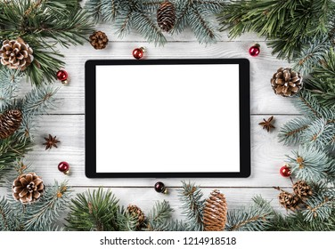 creative layout frame made of christmas tree branches pine cones and tablet pc on white