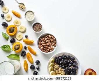 Creative layout of fresh summer fruits, muesli, nuts and grains on a white background with space for text. Healthy food. Useful breakfast. View from above.