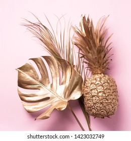 Creative layout. Gold pineapple and golden palm, monstera on pink background with copy space. Top view. Tropical flat lay. Exotic food concept, crazy trend. Banner.