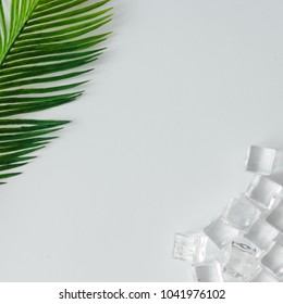 Creative layout of ice cubes and palm leaves on bright background. Flat lay summer drink minimal concept.