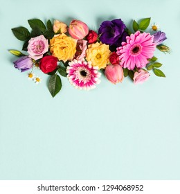 Creative layout made with beautiful flowers on blue background.