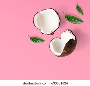 Creative layout made of coconuts and leaves. Flat lay. Food concept. Coconut on pink background.