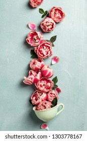 Creative layout made of coffee or tea cup with pink flowers on b