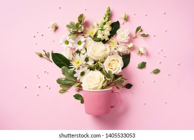 Creative layout made of coffee or tea cup with pink flowers. Fla