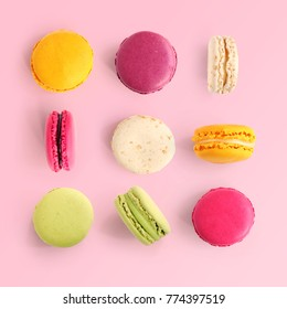 Creative layout made of colorful macaroons on the pink background. Flat lay. Food concept.