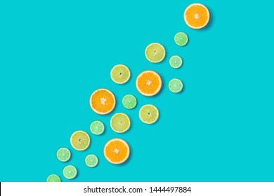 Creative layout made of colorful tropical fruits isolated on blue background. Minimal summer concept. Citrus fruit  pattern.  Pop art, flat lay, top view. Orange, Lime, Lemon slices background.